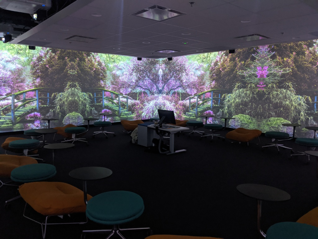 An image of a purple garden projected onto walls of the Immersion Studio